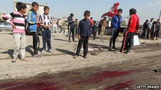 Children at the scene of a car bomb in Baghdad (Feb 2013)