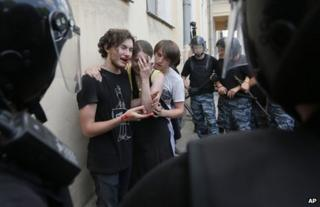 Russian police guard gay rights activists after they were attacked by rival protesters in St Petersburg, 29 June 2013