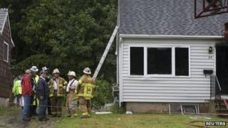 Emergency personnel gather at the site of a plane crash in East Haven
