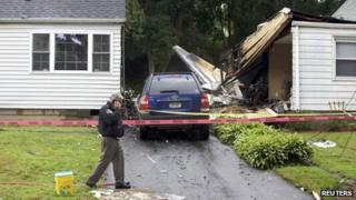 The remains of a plane is seen next to a damaged home after it crashed in East Haven