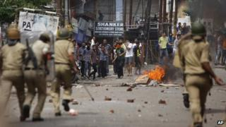 Indian policemen chase Hindus protesting against the state government after rival communities clashed in Kishtwar