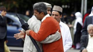 Worshipers embrace outside the mosque