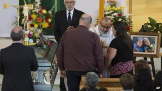 Father Maurice Frenette talks with Mandy Trecartin and Andrew Barthe at the funeral for their sons Noah and Connor Barthe, 10 August, Campbellton, New Brunswick.