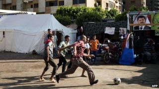 Egyptians play football outside the Rabaa al-Adawiya mosque in Cairo (10 August 2013)