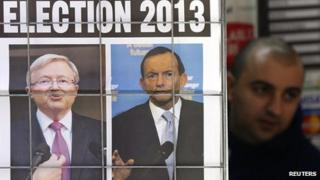 A man walks behind a newspaper ad picturing Australian Prime Minister Kevin Rudd (L) and opposition leader Tony Abbott in Sydney on 5 August 2013