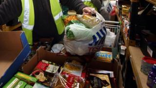 man bagging up at food bank