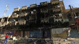 A boy looks at the site of a car bomb attack in the Shaab neighbourhood of northern Baghdad