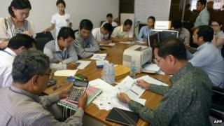 Cambodian National Election Committee (NEC) officers and representatives from political parties and non-government organisations verify election results at the NEC office in Phnom Penh on 3 August 2013