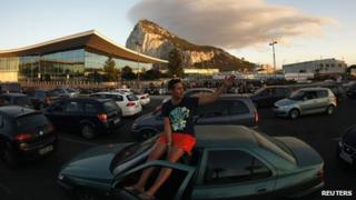 A man sits on his car roof with the Rock of Gibraltar in the background