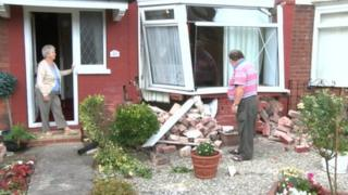 Iris and Tony Baxter examining damage to Mrs Baxter's home on Parkfield Drive, Hull