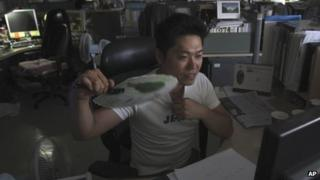A South Korean Ministry of Security and Public Administration official fans himself while working in darkness and without air conditioning