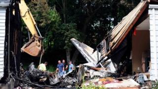 Officials inspect the debris of the plane crash 10 August 2013