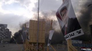 A poster of deposed Islamist President Mohamed Morsi is pictured in front of rising smoke
