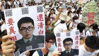 """In this image taken on 20 July 2013, in Taipei, Taiwan, protesters hold posters that read """"Give the truth"""" next to portraits of Taiwan soldier Hung Chung-chiu, who died in early July after being forced to perform a vigorous regime of calisthenics in sweltering heat on a base in suburban Taipei"""
