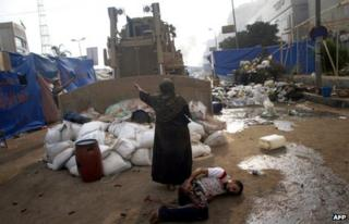 An Egyptian woman tries to stop a military bulldozer from hurting a wounded youth