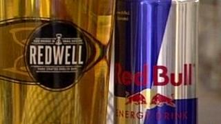 Pint of Redwell beer and can of Red Bull energy drink