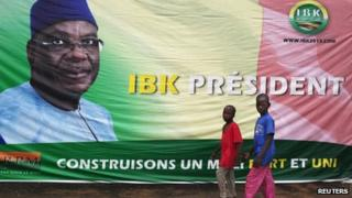 Boys walk in front of a poster of Mali's President-elect Ibrahim Boubacar Keita in Bamako 13 August, 2013.