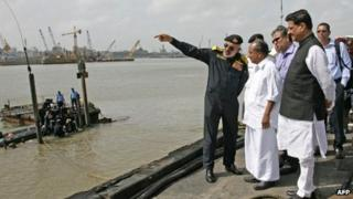 In this handout photograph released by the Ministry of Defence, Chief for Indian Naval Staff, Admiral D.K. Joshi (L) briefs Indian Defence Minister A.K. Antony (C) at the scene as Indian Navy personnel work at the conning tower of the stricken INS Sindhurakshak, after the submarine sank following an explosion at the naval dockyard in Mumbai on August 14, 2013
