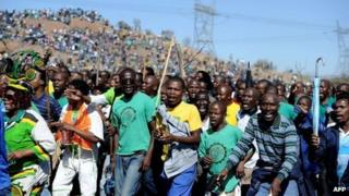 Co-workers and relatives of 34 miners shot dead by South African police during a violent wage strike sing and dance as they gather on August 16, 2013 in Marikana to mark the first anniversary of their deaths.