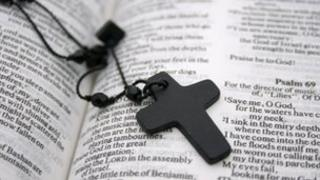 A crucifix necklace lying on an open Bible