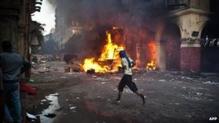 A supporter of the Muslim Brotherhood runs past a burning vehicle during clashes with security officers close to Cairo's Ramses Square (16 August 2013)