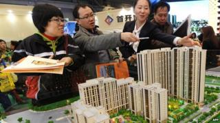 Buyers looking at a model of a new home development in China
