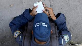 A policeman - viewed from above - writing notes in his book