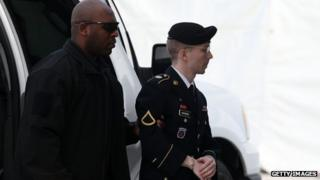 US Army Private First Class Bradley Manning is escorted by military police as he arrives for his sentencing at military court facility for the sentencing phase of his trial in Fort Meade, Maryland on 21 August 2013