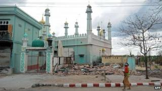 A woman with a child walks past a damaged mosque in Meiktila. Photo: June 2013