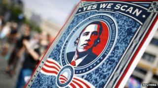 "A protester holds a placard showing U.S. President Barack Obama with the phrase ""Yes we scan"""