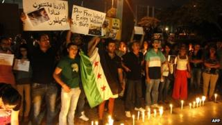 Lebanese and Syrian civilians hold signs and Syria's former independence flag as they take part in a candle-lit vigil in front of the offices of the United Nations headquarters in Beirut