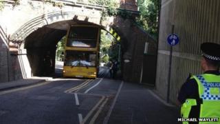 Bus stuck under bridge