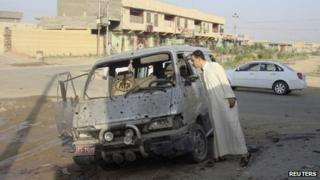 A man inspects a damaged vehicle a day after a car bomb attack in Dujail (23 August 2013)