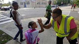 A little girl is greeted by a Safe Passage worker on her way to elementary school in Chicago, Illinois on 26 August 2013
