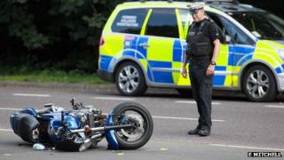 Motorcycle with police officer looking at it