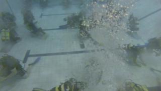 Divers playing dominoes underwater