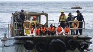 Australian customs officials and navy personnel escort asylum-seekers onto Christmas Island on 21 August 2013