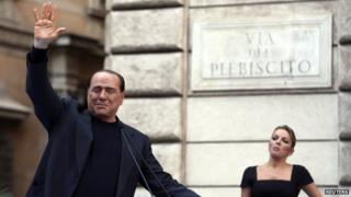 Former Italian Prime Minister Silvio Berlusconi waves to supporters as his girlfriend Francesca Pascale looks on during a rally to protest his tax fraud conviction, outside his palace in central Rome on 4 August, 2013.