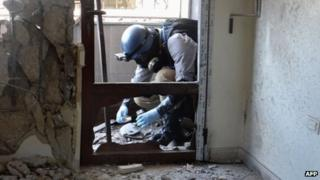 A United Nations (UN) arms expert collects samples as they inspect the site where rockets had fallen in Damascus eastern Ghouta during an investigation into a suspected chemical weapons strike near the capital taken on 29 August 2013.