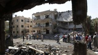 People inspect the damage at a site hit by what activists say was a car bomb in Raqqa province, eastern Syria August 29, 2013.