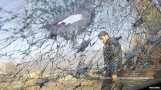 A policeman is seen through the damaged windshield of a car in Srinagar in this March 10, 2011 file photo
