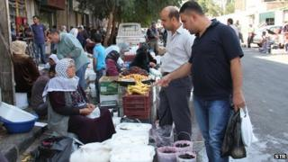 Syrians shop at al-Fahameh market in Damascus