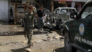 An Afghanistan security forces member gestures at the site of a suicide attack