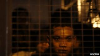 A detained suspected illegal migrant worker from Indonesia sits in an immigration truck during a crackdown on illegal migrant workers in Kelang, outside Kuala Lumpur September 1, 2013