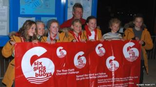 Six girls and 2 adults celebrating after the girls swam the channel, they are holding a banner