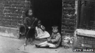 Children playing outside their slum home in London in 1910