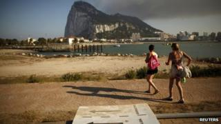 Two Spanish tourists walk past a broken traffic signal lying on the ground as they try to find the correct direction to the Spanish border to enter the British territory of Gibraltar