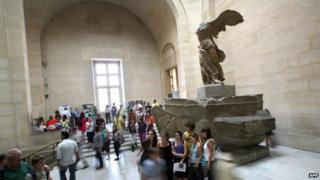 A picture taken on 17 June, 2009, shows people posing in front of the Winged Victory of Samothrace sculpture as they visit the Louvre museum in Paris.