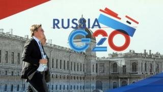 Men walk past a banner with the logo of G20 Summit in Saint Petersburg on September 4, 2013 ahead of the G20 Summit starting on Thursday