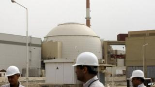 Iranian technicians walk outside the building housing the reactor of Bushehr nuclear power plant